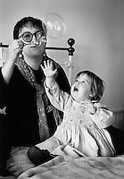 Portrait of a mother and young child sitting on a bed blowing bubbles.