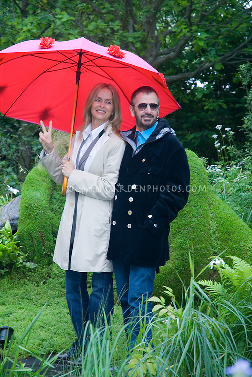 Ringo Starr & wife Barbara Bach under red umbrella, flashing peace sign & smiling in garden together, showing full figures, 2006