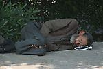 Homeless elderly man asleep on the sidewalk