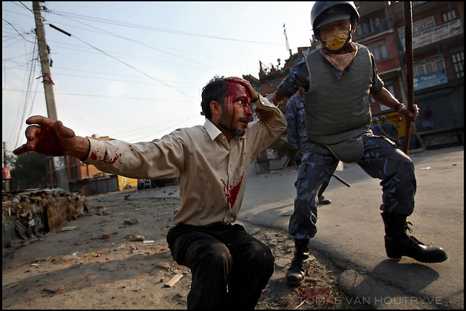 A riot police officer grabs the arm of a pro-democracy protester with a head injury, after police clashed with demonstrators in Kathmandu, Nepal on 16 April, 2006. Police fired shotguns and tear gas to drive back thousands of protesters marching against King Gyanendra's absolute rule.<br />