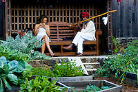 Young multi-ethnic woman and African-American man playing flute in organic garden setting