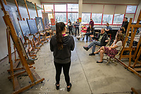 Kimberlyn Sheldon presents her paintings to faculty and fellow Bachelor of Fine Arts (BFA) students during a BFA check-in and critique session in UAA's Fine Arts Building.