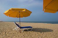 Lounge chair sits under umbrella on beach