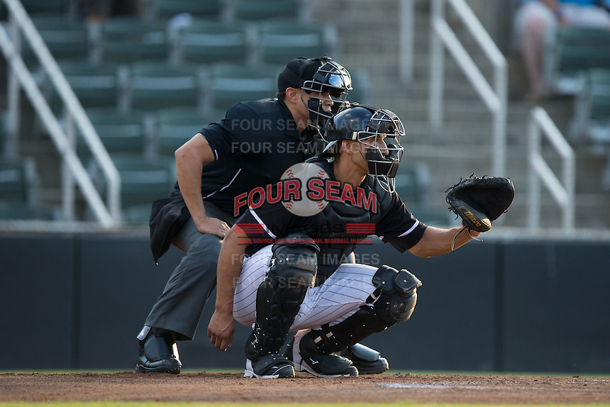 Kannapolis Intimidators catcher Seby Zavala (21) sets a target as home plate umpire David Martinez looks over his shoulder during the game against the Lakewood BlueClaws at Kannapolis Intimidators Stadium on May 10, 2016 in Kannapolis, North Carolina.  The BlueClaws defeated the Intimidators 5-3.  (Brian Westerholt/Four Seam Images)