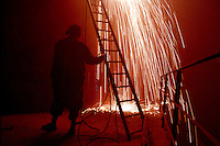 A worker holds a ladder for the welders working above at the ship-breaking yard in Gaddani.