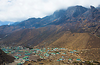 Nepal The village of Khumjung with the cloud-topped Himalayas rising steeply above it. remote, Mt Everest, Himalayas