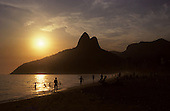 Rio de Janeiro, Brazil. Sun setting behind the Dois Irmaos (Two Brothers) mountain with people on the beach.