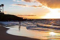 Two children play in the water at sunset, Wailea Beach, Maui.