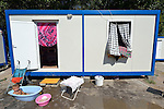 """THIS PHOTO IS AVAILABLE AS A PRINT OR FOR PERSONAL USE. CLICK ON """"ADD TO CART"""" TO SEE PRICING OPTIONS.   A small child bathes outside the shipping container that has been converted into its family's home home in Makis, a village outside of Belgrade, Serbia. This and dozens of other Roma families were evicted from Bellville, an urban squatter settlement, in 2012 to make way for construction of new apartments and office buildings. The shipping containers they now call home, which were provided at no cost by local authorities, are far from the city center."""