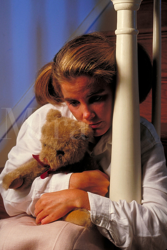Depressed woman sitting on steps while holding a teddy bear.