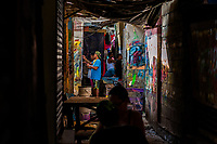 "Colombian sign painter work on music party posters in the sign painting workshop in Cartagena, Colombia, 11 December 2017. Hidden in the dark, narrow alleys of Bazurto market, a group of dozen young men gathered around José Corredor (""Runner""), the master painter, produce every day hundreds of hand-painted posters. Although the vast majority of the production is designed for a cheap visual promotion of popular Champeta music parties, held every weekend around the city, Runner and his apprentices also create other graphic design artworks, based on brush lettering technique. Using simple brushes and bright paints, the artisanal workshop keeps the traditional sign painting art alive."