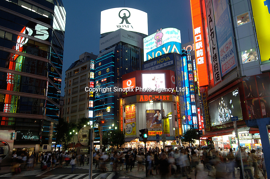 Crowds get ready to cross the intersection at Shinjuku-dori Avenue in the Shinjuku district of Tokyo, Japan. It is full of entertainment and shopping areas. Department store, electronics, restaurants and bars can be found most in this area..27 Jul 2006
