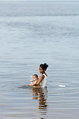 Altamira, Brazil. Caboclo woman bathing her baby in the Xingu River.