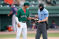 No one but team and staff on the field due to COVID-19 means no bat boys or bat girls. So, someone has to take new baseballs to the umpires. Here Brandon Howlett of the Greenville Drive (35) delivers to umpire Ervin Johnson on Sunday, May 9, 2021, at Fluor Field at the West End in Greenville, South Carolina. (Tom Priddy/Four Seam Images)