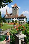 CHE, Schweiz, Kanton Bern, Berner Oberland, Spiez: Schloss Spiez am Thunersee - Frau sitzt auf Bank | CHE, Switzerland, Bern Canton, Bernese Oberland, Spiez: castle Spiez at Lake Thun - woman sitting on bench