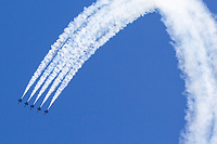 The Blue Angels F/A-18 Hornets perform a loop maneuver in line abreast formation.
