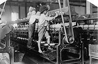 Macon, Georgia. USA - 1909 January 19.<br /> <br /> Many youngsters here. Some boys were so small they had to climb up on the spinning frame to mend the broken threads and put back the empty bobbins. Location: Macon, Georgia.