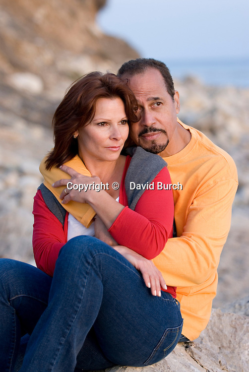 Mature couple sitting at beach, he looking concerned