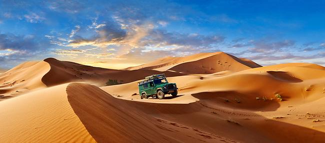 Land Rover Defender amongst the Sahara sand dunes of erg Chebbi, Morocco, Africa