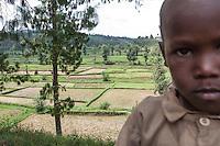 """""""Rice is my favorite food, but when I'm grown I'll be  a soldier. Farmers don't get much money and with a soldier's pay I can buy all the rice I want."""" -Simon Majyambere on the road to Butare above a rice paddy. Photo by Brendan Bannon Rwanda, Feb. 27, 2014."""