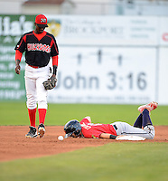 State College Spikes second baseman Bruce Caldwell (13) lays on the ground after getting hit by the throw sliding in on a stolen base as shortstop Javier Lopez (35) retrieves the ball during a game against the Batavia Muckdogs on July 29, 2013 at Dwyer Stadium in Batavia, New York.  State College defeated Batavia 2-1.  (Mike Janes/Four Seam Images)