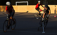 17 AUG 2014 - LONDON, GBR - A player from Mondial (left, in red and black) shoots during the final against Triple Jay (in black) at the 2014 London Open Bike Polo tournament in Highbury Fields in London, Great Britain (PHOTO COPYRIGHT © 2014 NIGEL FARROW, ALL RIGHTS RESERVED)