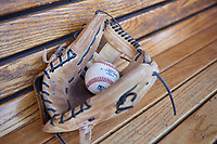 A minor league baseball rests inside a glove in the dugout before an Arizona League game between the AZL Brewers Blue and AZL Brewers Gold on July 13, 2019 at American Family Fields of Phoenix in Phoenix, Arizona. The AZL Brewers Blue defeated the AZL Brewers Gold 6-0. (Zachary Lucy/Four Seam Images)