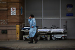 A medical worker takes a smoke break in front of Maimonides Medical Center on March 28, 2020 in Brooklyn, NY.  NYC's daily death toll from the coronavirus nearly tripled from the previous 24-hour period from 85 on Friday to 222 on Saturday.  Photograph by Michael Nagle/Redux