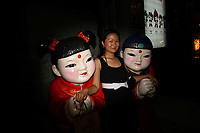 CHINA. Beijing. A woman posing for a picture with two statues in the shopping district of Wangfujing, a popular place for spectators, tourists and athletes to visit during the Olympic Games. 2008