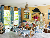 The table and chairs were finds from Circa Who in Palm Beach. They sit beneath a dominating shell chandelier, which features an unexpected antiqued silver finish. The mounted game fish, a throwback to 1970s beach décor, adds whimsy to what could otherwise be a more formal room.