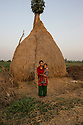 """Nepal - Meghauli - Sanju Bhatta, 29, in her house in the village of Meghauli, in the Central district of Chitwan. Bhatta lives alone with her four kids, aged from ten to two, after her husband Rameshwar Bhatta left to work in Qatar as a driver one week ago. The couple has been married for 11 years. Rameshwar left Nepal to repay the loan the family took to build their house, leaving Sanju to look after their fields and small store. """"I am alone. I have to cook, farm, feed the animals and raise the kids all by myself. They frequently ask me about their father"""" she says. Rameshwar frequently calls her. """"The only think he complains about is that he has to work so hard for such a small amount of money""""."""