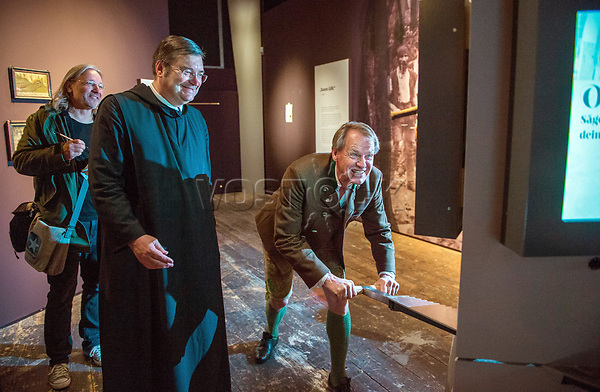 26 April 2018, Germany, Ettal: Johannes Bauer (c), padre at Ettal Abbey and Markus Wasmeier (r), former German ski racer, playing a sawing game during a press tour at the Bayerische Landesausstellung 2018 (lit. Bavarian State Exhibition 2018). The state exhibition is set to open on 02 May. Photo: Lino Mirgeler/dpa