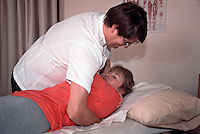 Osteopath performing manipulation of lumbar spine, side roll, on a patient. This image may only be used to portray the subject in a positive manner..©shoutpictures.com..john@shoutpictures.com