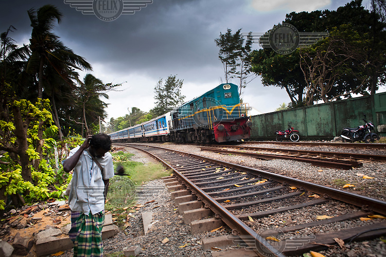 A man walks along train tracks as a train travels past as he makes his way to Mt Lavinia, a suburb of Colombo.