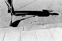 Switzerland. Geneva. Garbage collectors. Streets cleaning. Shadow of a street sweeper and a broom. Cigarettes on the street. © 1991 Didier Ruef