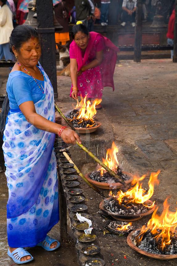 Woman making fires to worship in Hindu religion at Nyatapola Temple in village of Bhaktapur a town near Kathmandu Nepal