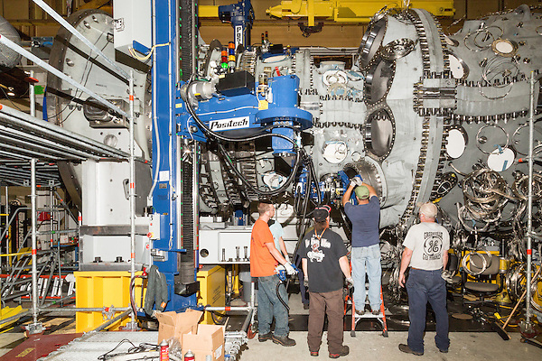 July 6, 2016. Greenville, South Carolina. <br />  Workers install the combustion cans on a 7HA.02 model GE gas turbine, with the help of a custom Positech robot arm.  The arm has been used for only a year, and has greatly helped with the assembly process of these large turbines.<br />  At the General Electric Gas Turbine factory, engineers  design, produce, test and repair gas turbines for generating electricity. These turbines weigh more than 900,000 pounds and can create internal combustion temperatures up to 2,900 degrees F. Depending on the model, one of the GE turbines can produce enough electricity for half a million American households.