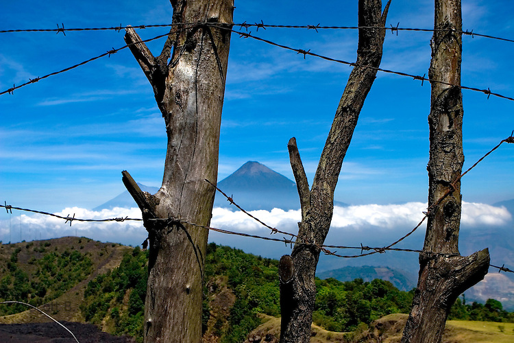 The cone of Volcan Agua through a fence from the still active Volcan de Pacaya, near Guatemala City and Antigua