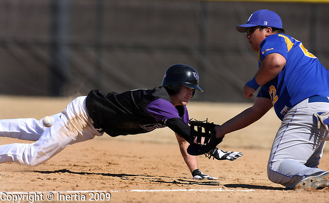 SIOUX FALLS, SD - MARCH 18:  Myles Kuiper #1 of the University of Sioux Falls dives back to first on a pick off attempt as Armando Rodriguez #22 of Dakota State waits for the ball during the Cougars home opener Wednesday afternoon at Harmadon Park. (Photo by Dave Eggen/Inertia)