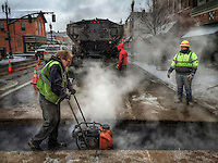 Steam rises from hot asphalt land into a trench cut into State Street in Uptown Westerville to repair a sewer line.