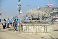 NEPAL, Terai, Chitwan Nationalpark, town Tandi, Rhino sculpture and damaged road with dust / Nepal, Terai, Chitwan Nationalpark, Stadt Tandi, Nashorn Skulptur und kaputte Strasse mit viel Staub