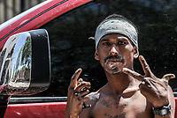 Un pandillero sin camisa y con pañuelo en la cabeza hace una señales con sun manos para marcar territorio al momento que utiliza un espejo retrovisor de una camioneta para rasurare la cara.