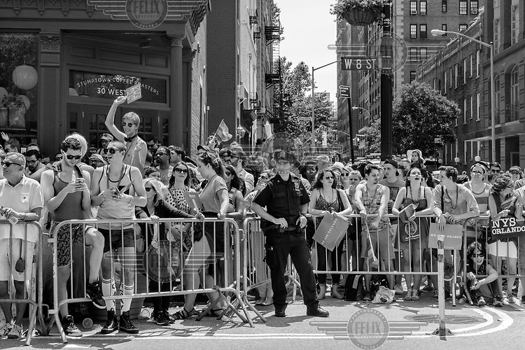 Spectators line the street at the Gay Pride parade.