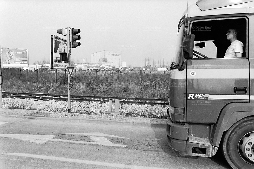France. Saône-et-Loire department. Chalon-sur-Saône. A truck driver and his lorry outside the Kodak factory. Eastman Kodak Company. Traffic lights. Chalon-sur-Saône is located in the south of the Burgundy region. © 1996 Didier Ruef ..