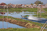 Myanmar, Burma.  Motorized Boat Speeds through the Waterways of Inle Lake, Shan State.  Note power lines bringing electricity to village houses.