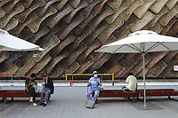 Visitors sit in front of an elaborately designed pavilion at the Shanghai World Expo.