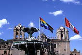Cusco, Peru. Fountain in the Plaza de Armas with swans; rainbow flag of Cusco and Peruvian national flag behind.