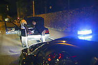 """Switzerland. The Republic and Canton of Neuchâtel. Neuchâtel. Narcotics squad. """"Narko"""" operation. Blue emergency light on the roof of a police car riding down the street at night. Two police officers on duty (both in plain-clothes) control te car and identities of two french black men. The policemen look for illegal substances (drugs). Both black men will be left free at the end of the control. Plainclothes law enforcement is a method used by police. The policemen wear plainclothes or """"ordinary clothes"""" instead of a uniform in order to avoid detection or identification as law enforcement agents. Police officers in plainclothes must identify themselves when using their police powers. 9.04.15 © 2015 Didier Ruef"""