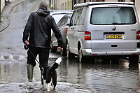 A man walks his dog in a flooded road caused by heavy rain in Crickhowell, south Wales, UK. Saturday 26 October 2019