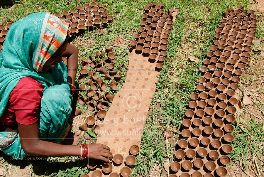 INDIA, Jharkhand, Sarwan, village Bhatkundi, potter makes one-way tea cups from clay, which are used for chai, woman dry cups in the sun / INDIEN Jharkand , Sarwan, Dorf Bhatkundi, Toepfer stellt Einweg Teetassen aus Ton her, Frau trocknet Teetassen in der Sonne